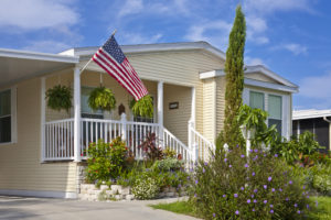 Yellow double-wide mobile home with American flag