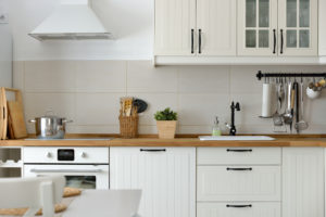 kitchen with white cupboards, wood block counter and black hardware